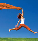 Woman leaping in the air trailing a orange cloth